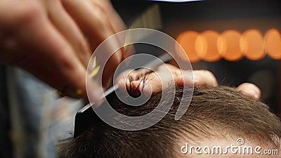 Hombre barbero cortando el pelo del hombre con tijeras y peine Funcionador de pelo que sirve al cliente Hombre estiloso sentado e almacen de metraje de vídeo