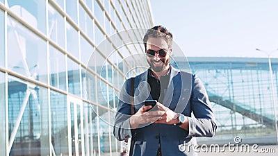 Hombre barbudo elegante en gafas de sol usando el dispositivo mientras que pasa por el terminal de aeropuerto, sonrisas al texto  metrajes