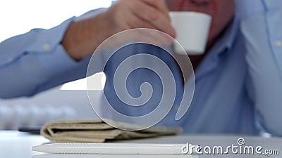 Hombre cansado que duerme con la cabeza en las estelas de la tabla para arriba para tomar un sorbo de café almacen de video