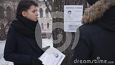 Hombre caucásico colgando el anuncio de su hijo desaparecido en el árbol como su disgustada esposa parado con otros folletos Gent almacen de video