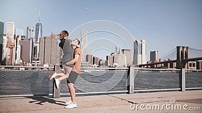 Hombre caucásico feliz que encuentra a su novia, abrazando y sonriendo en el horizonte soleado de Manhattan en la cámara lenta de almacen de metraje de vídeo