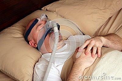 Hombre con apnea de sueño usando una máquina de CPAP