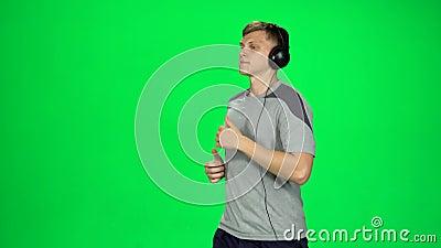 Hombre con grandes auriculares negros está corriendo, Chroma Key almacen de metraje de vídeo