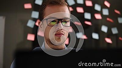 Hombre con la computadora portátil Hombre joven en el funcionamiento de vidrios en un ordenador portátil en la oficina Hombre de  almacen de metraje de vídeo