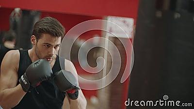 Hombre de la aptitud en los guantes que hacen soplos en bolso del combate en el entrenamiento del boxeo en gimnasio metrajes