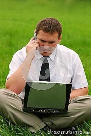 Hombre de negocios con la computadora portátil que se sienta en la hierba