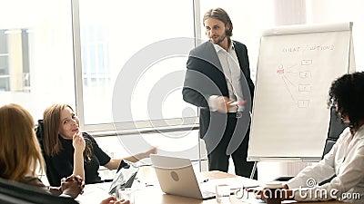 Hombre de negocios confiado que da la presentación en flipchart a los colegas en la sala de reunión almacen de video