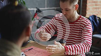Hombre de negocios joven del inconformista que explica los detalles del proyecto al equipo étnico multi que muestra el plan de pa almacen de metraje de vídeo