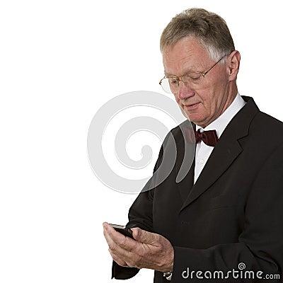 Hombre de negocios mayor que manda un SMS en el teléfono móvil