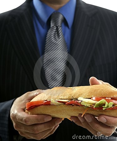 Hombre de negocios que come los alimentos de preparación rápida de los desperdicios