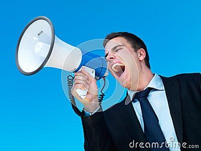 Hombre de negocios que grita en el megáfono con el cielo