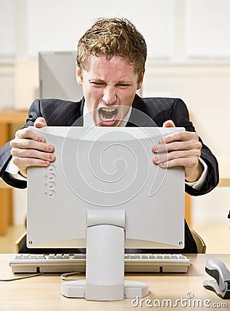 Hombre de negocios que grita en el ordenador