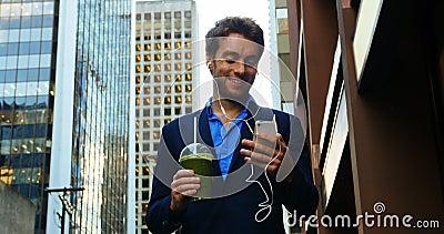 Hombre de negocios que habla en el teléfono móvil mientras que comiendo jugo almacen de metraje de vídeo