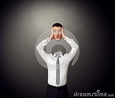 Hombre de negocios que lleva a cabo a su cabeza sorprendente en manos
