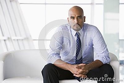 Hombre de negocios que se sienta en el sofá en pasillo