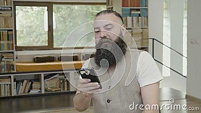 Hombre de negocios sonriente feliz con la barba que celebra éxito y la victoria después de enrollar su teléfono elegante en la of metrajes