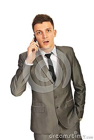 Hombre de negocios sorprendente por una llamada de teléfono