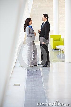 Hombre de negocios y empresarias que hablan en oficina moderna