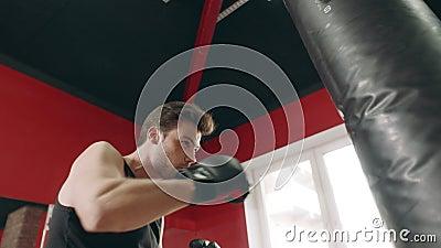 Hombre del boxeador que golpea el bolso del combate con el pie en la opinión de ángulo bajo del gimnasio almacen de video