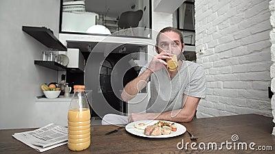 Hombre del desayuno que vierte la comida de Juice Into Glass And Eating en casa almacen de metraje de vídeo