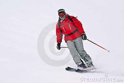 Hombre del esquiador que se ejecuta abajo del centro turístico nevoso MES del invierno