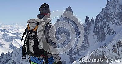 Hombre del montañés del escalador que alcanza el top nevoso del soporte con el hacha de hielo en día soleado Actividad del esquí  almacen de video