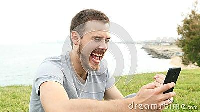Hombre emocionado que comprueba mensajes de teléfono