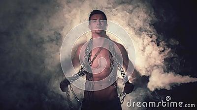 Hombre en cadenas del metal en humo almacen de metraje de vídeo