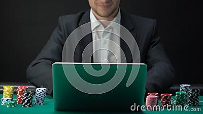 Hombre en juego del traje en línea en el ordenador portátil, sosteniendo el microprocesador del casino disponible, apostando almacen de metraje de vídeo