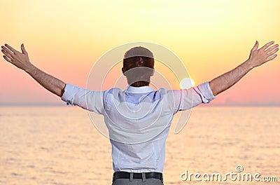 Hombre en la salida del sol del mar