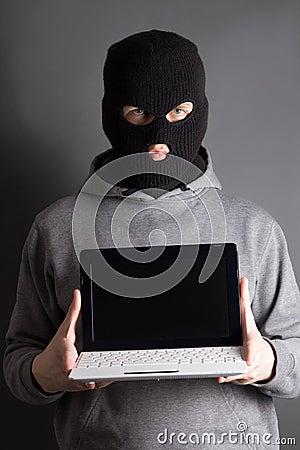 Hombre enmascarado con el ordenador sobre gris