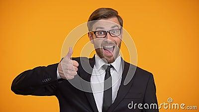 Hombre feliz en el traje que muestra los pulgares para arriba y que guiña en la cámara, buen asunto almacen de metraje de vídeo