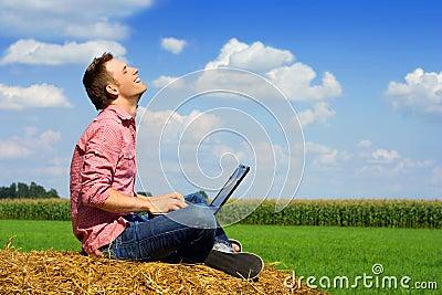 Hombre hermoso con el ordenador