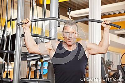 Hombre hermoso en sus años  40 que ejercita en gimnasia