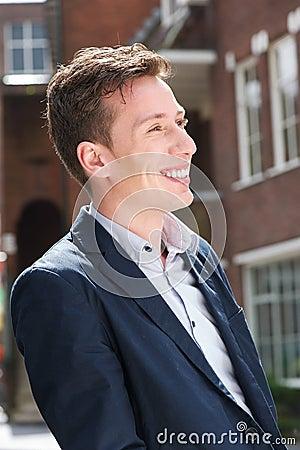 Hombre joven atractivo en chaqueta azul que sonríe al aire libre
