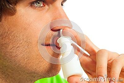 Hombre joven con el aerosol nasal