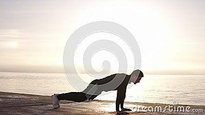 Hombre joven fuerte que hace ejercicio complejo - pectorales y saltos para arriba, en la cámara lenta Entrenamiento del entrenami almacen de video