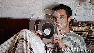 Hombre joven hermoso en cama que mecanografía en la tableta metrajes