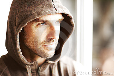 Hombre joven hermoso en la chaqueta del invierno que mira lejos
