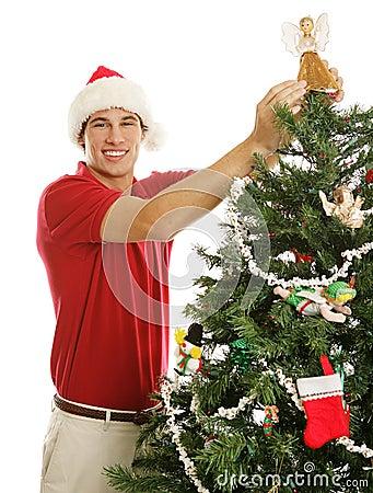 Hombre joven que adorna el árbol de navidad
