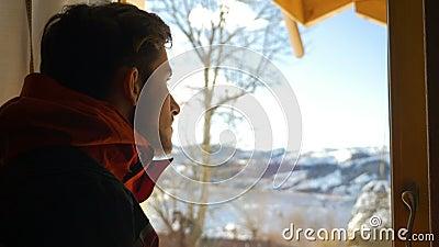 Hombre joven que considera hacia fuera la ventana el paisaje hermoso en invierno almacen de video