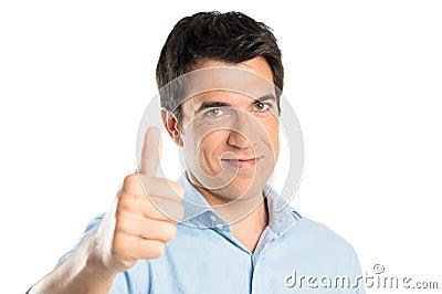 Hombre joven que gesticula el pulgar encima de la muestra