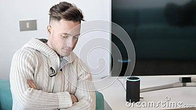 Hombre joven que habla al ayudante electrónico elegante del hogar del altavoz almacen de video