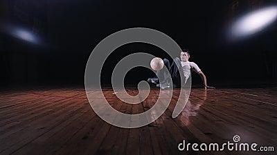 Hombre joven que hace fútbol del estilo libre en un fondo negro almacen de metraje de vídeo