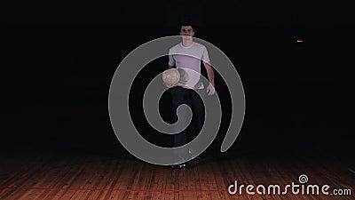 Hombre joven que hace fútbol del estilo libre en un fondo negro metrajes
