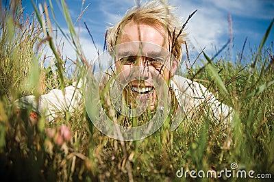 Hombre joven que oculta en la hierba
