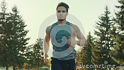 Hombre joven que se ejecuta en parque El activar del hombre del deporte al aire libre Parada cansada del corredor almacen de video
