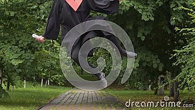 Hombre joven sonriente en vestido académico que camina y que salta, manera al éxito futuro almacen de video