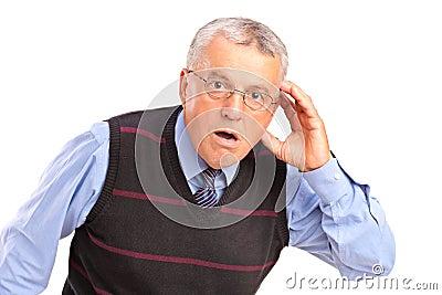 Hombre maduro que lleva a cabo su cabeza y que gesticula qué