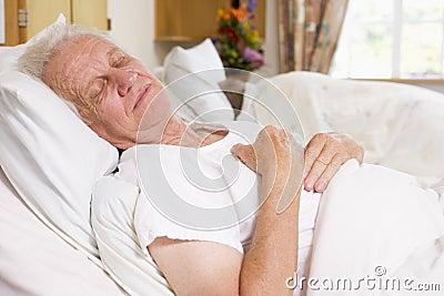 Hombre mayor dormido en cama de hospital Imagen de archivo